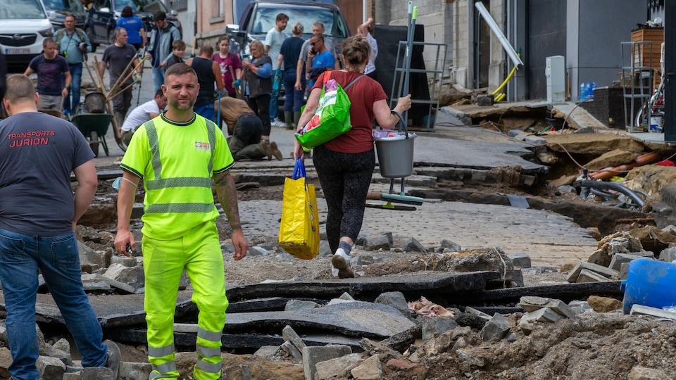 Des gens dans une rue détruite.