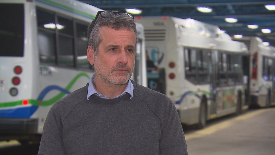Patrice Dupuis dans un garage devant des autobus.