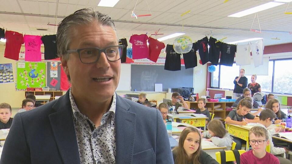 Yves Ouellet répond aux questions d'un journaliste dans une salle de classe.