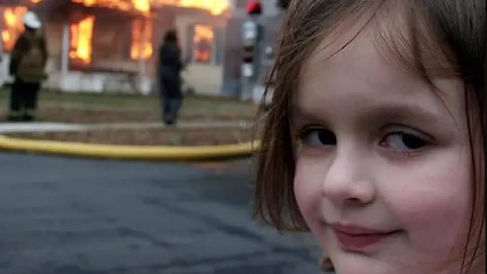 Une petite fille regarde l'objectif de la caméra avec un air coquin alors qu'un feu ravage une maison derrière elle.