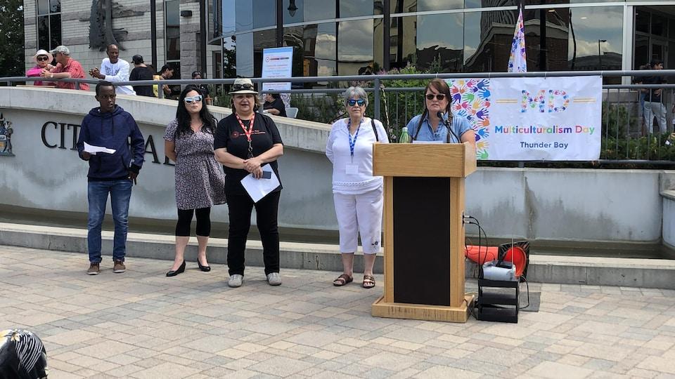 Un groupe de personnes près d'un podium devant un bâtiment.