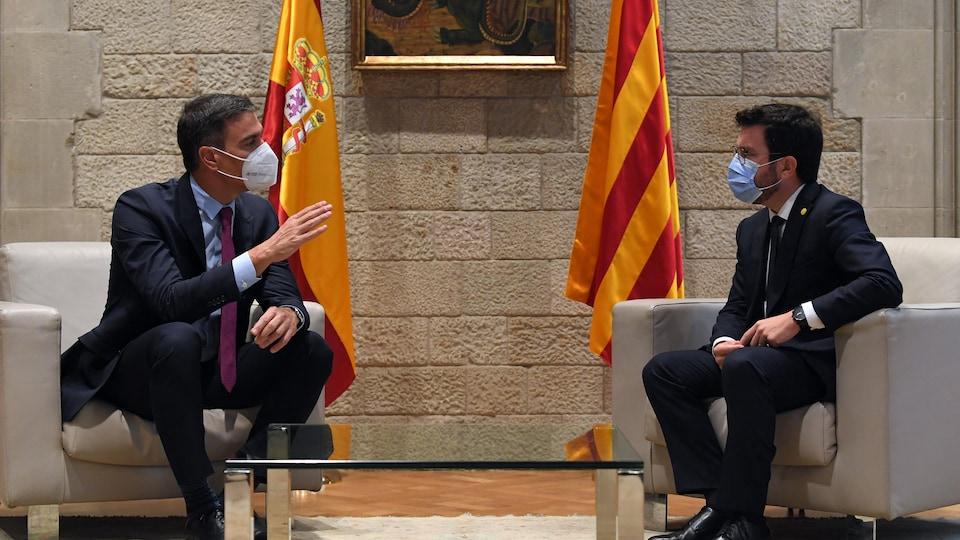 Pedro Sanchez et Pere Aragonès, masqués, discutent, assis dans des fauteuils.
