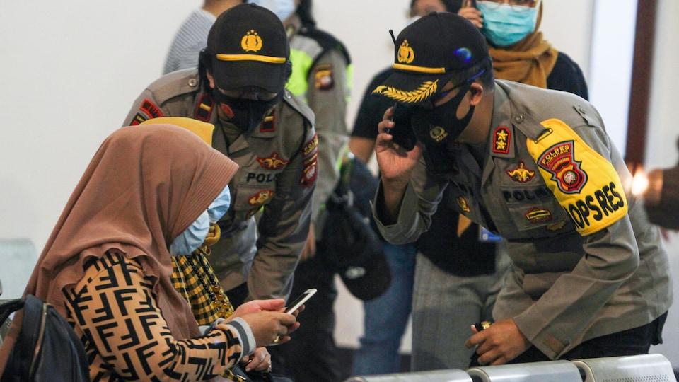 Des agents en uniforme parlent à des femmes voilées et portant des masques de protection dans un aéroport en Indonésie.