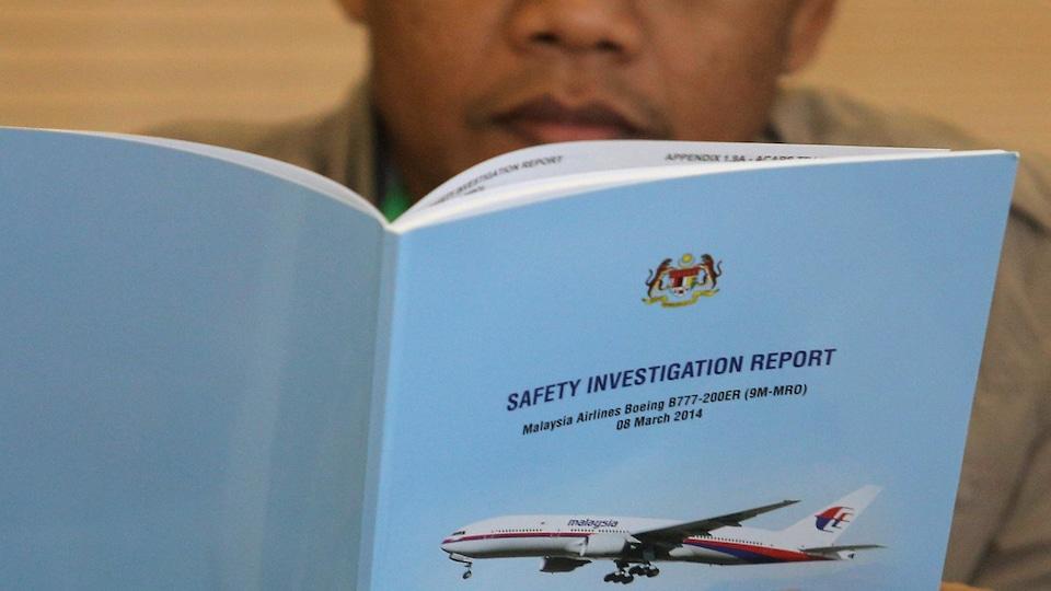 Un homme qui a perdu un proche dans la disparition du vol MH370 de Malaysia Airlines lit le rapport d'enquête sur les événements.