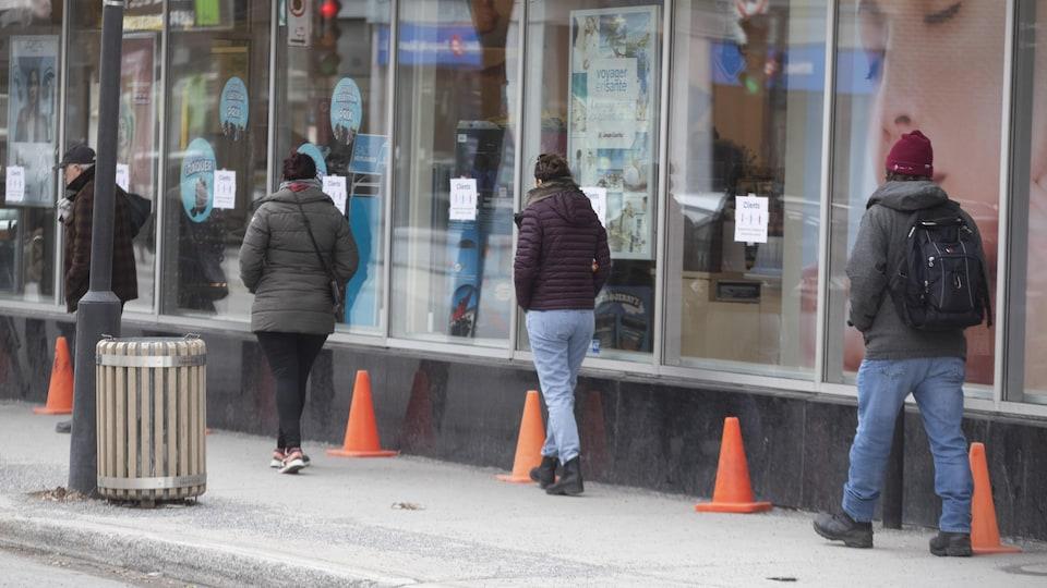 Des gens font la queue et gardent leurs distances devant une pharmacie.