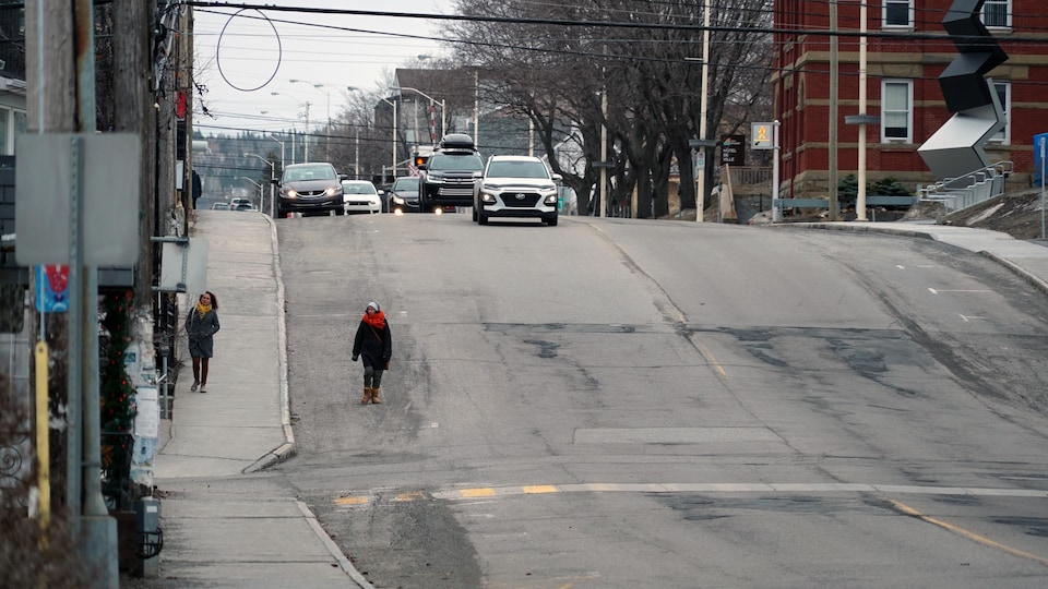Sur l'avenue de la Cathédrale à Rimouski, deux personnes marchent à la même hauteur, à une distance d'environ deux mètres l'une de l'autre.