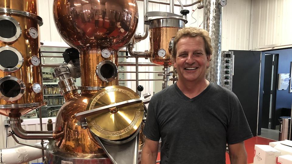 Philippe Harvey devant un appareil de distillerie.
