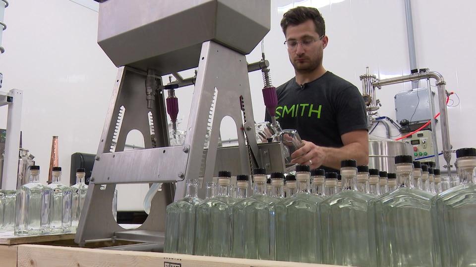 Michael Briand, cofondateur de la distillerie O'Dwyer, remplit des bouteilles de gin.