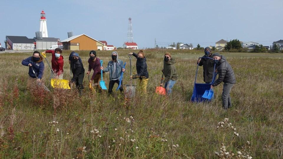 Neuf personnes de l'entreprise font la première pelletée de terre symbolique (avec des pelles à neige) sur le terrain près du phare de Pointe-au-Père.