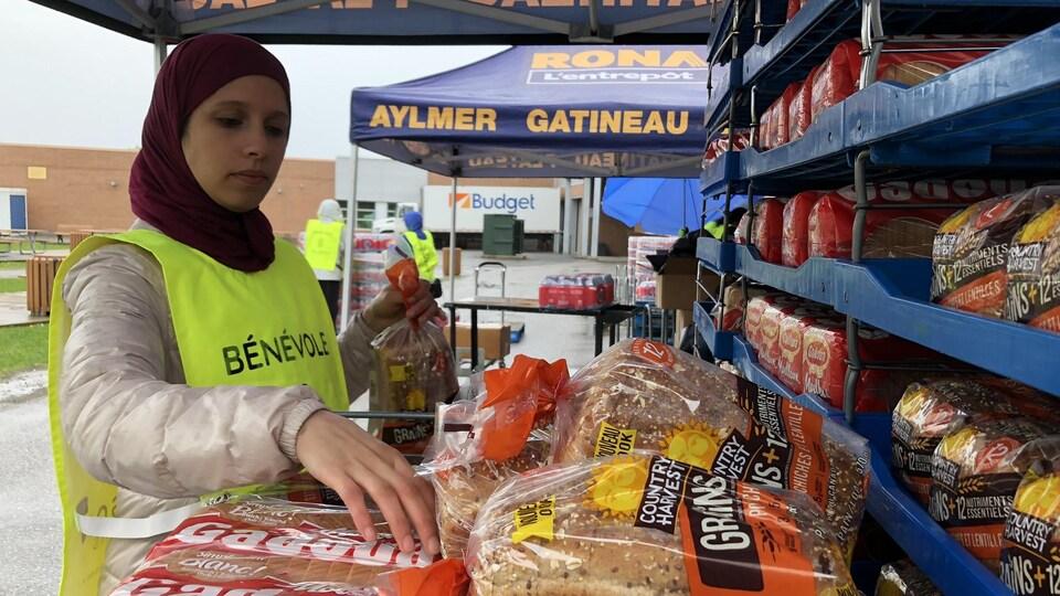 Une bénévole place des pains sur une étagère.