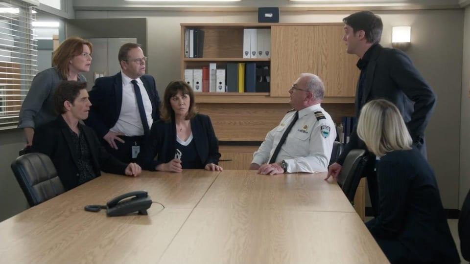 Sept personnes sont autour d'une table et semblent surprises.
