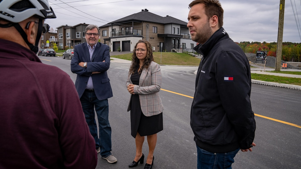 Les trois candidats au poste de conseiller du district du Carrefour  en discussion avec un résident du secteur.