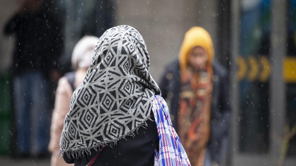 Une femme portant un voile marche sous une neige fine à Montréal.