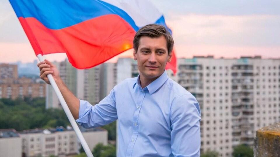 Dmitri Goudkov tient un drapeau russe dans ses mains.