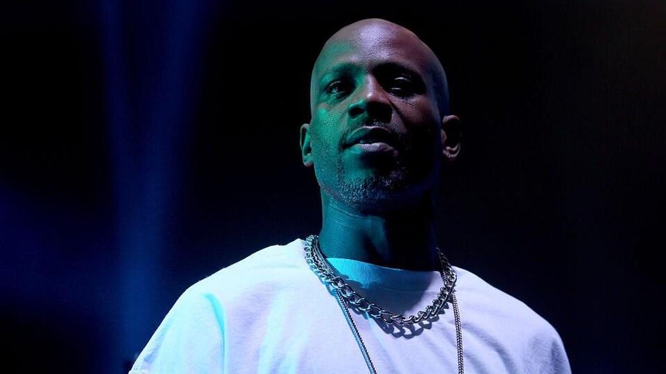 Un homme au crâne rasé qui porte une chaîne massive autour du cou sur un chandail blanc.