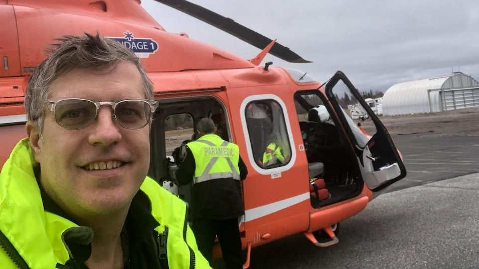 Le médecin urgentiste Sean Moore en tenue de travail pose devant un hélicoptère d'intervention rouge.