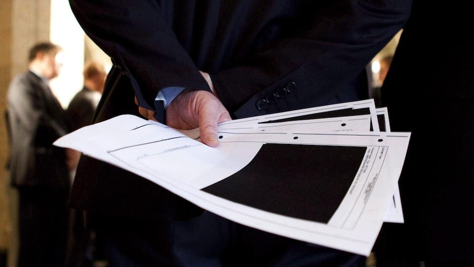 Un fonctionnaire fédéral tient dans une main des feuilles d'un document censuré.