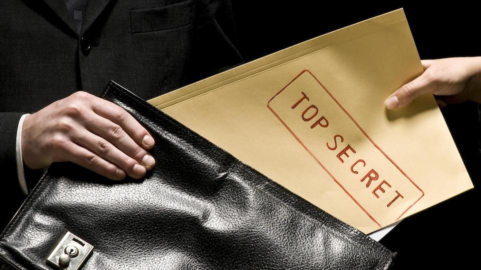 Deux personnes s'échangent des documents confidentiels.