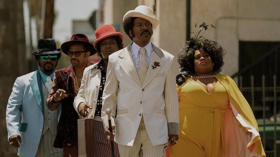 Quatre hommes et une femme qui portent des vêtements des années 70 et marchent dans la rue.