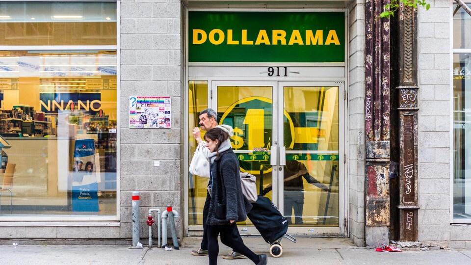 Des passants marchent devant l'entrée d'un magasin Dollarama.