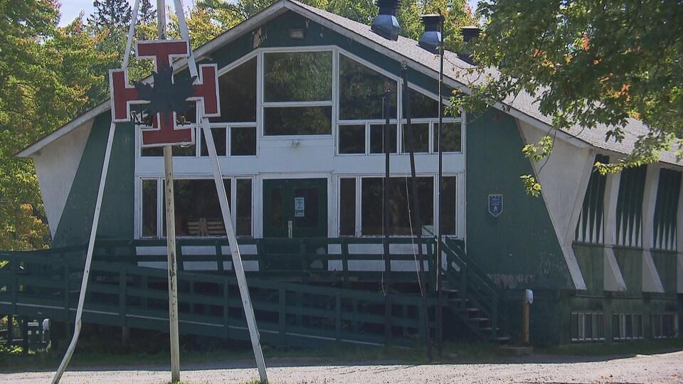 Bâtiment du Domaine scout avec symbole scout sur un poteau à l'avant-plan, en guise d'enseigne.
