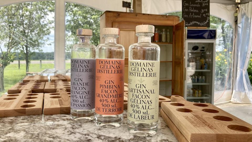 Trois bouteilles de gins sont sur un comptoir.