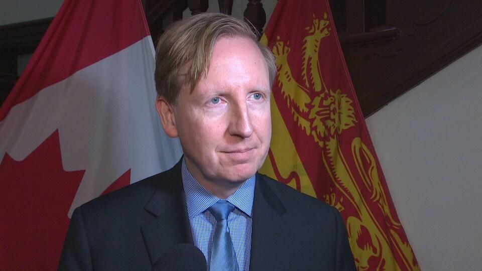 Dominic Cardy devant des drapeaux du Nouveau-Brunswick et du Canada.
