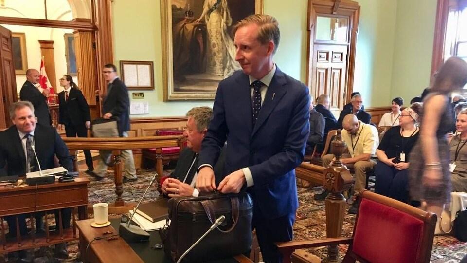 Un homme dépose sur une table une valise dans une salle bondée de gens.