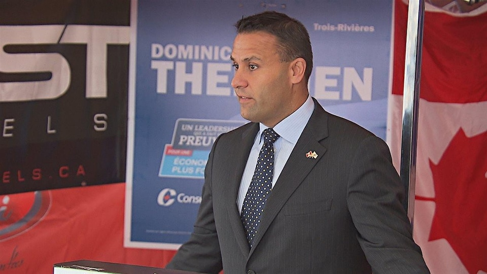 Le candidat conservateur Dominic Therrien devant un drapeau canadien et une affiche.