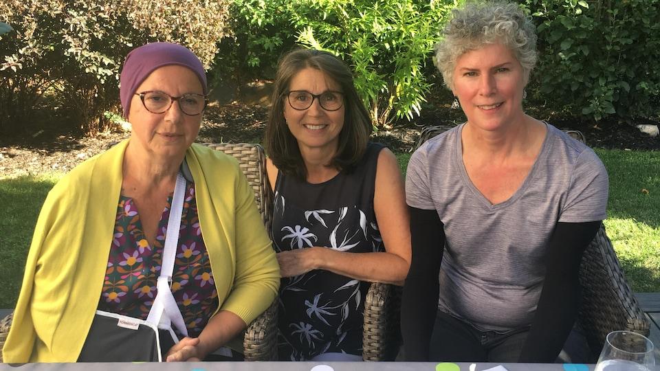 Trois femmes devant des buissons.