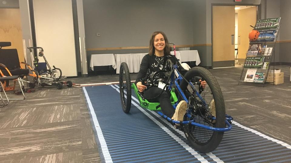 Une femme est assise dans un vélo adaptée aux personnes handicapées.