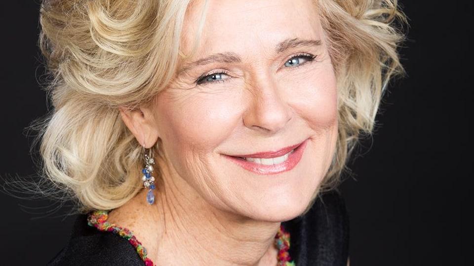 Portrait en couleur, sur fond noir, de Dominique Demers, souriante, buste tourné de trois-quarts. Elle est blonde, a les yeux clairs, porte des boucles d'oreilles et un haut noir avec un liseré fleuri.