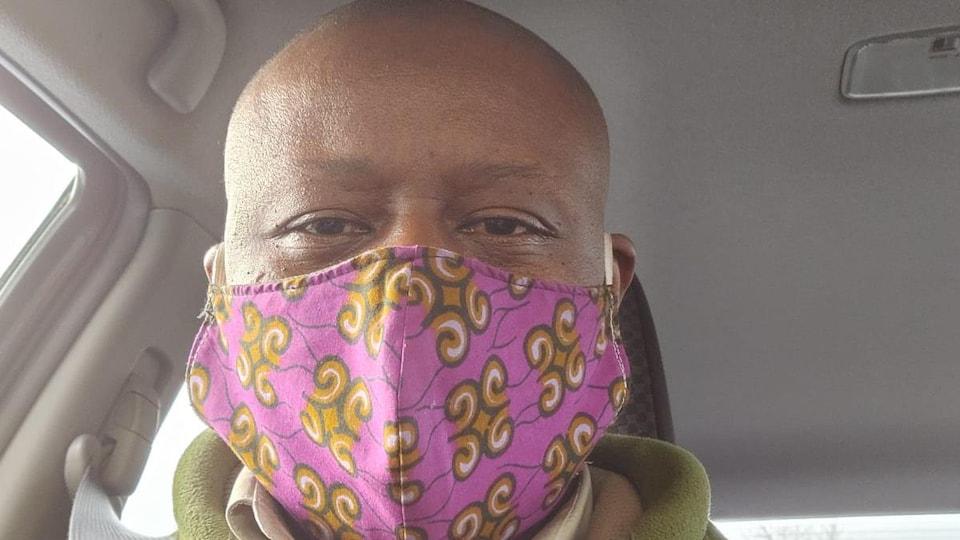 Un homme noir avec un masque dans une voiture.