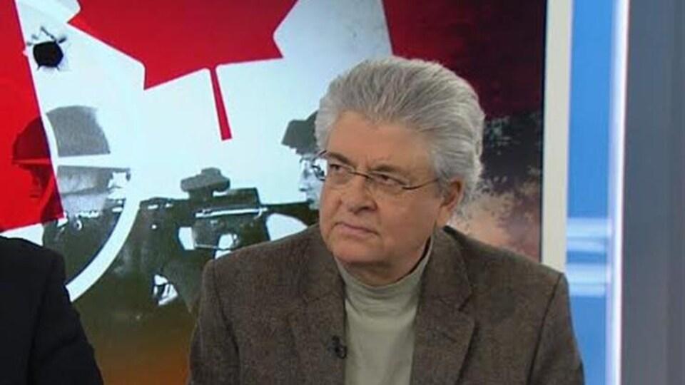 Dominique Peschard assis sur un plateau de télévision.