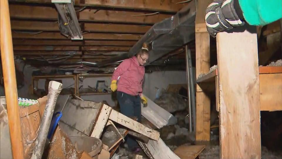 Des citoyens constatent l'étendue des dommages causés par les inondations dans leur sous-sol.