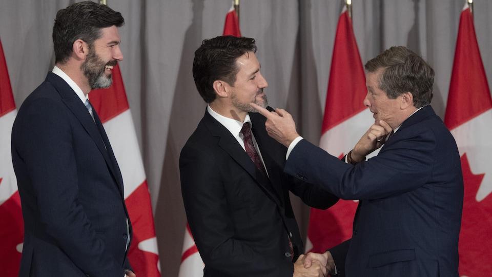 Le premier ministre canadien, Justin Trudeau, et le maire de Toronto, John Tory, se tiennent le menton sous le regard du maire d'Edmonton, Don Iveson, lors d'une rencontre des maires des grandes villes canadiennes à Ottawa, le 6 février 2020.
