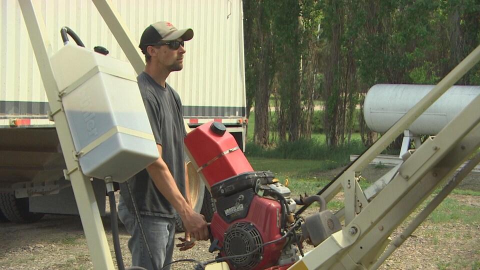 Don McLean manipule une machine agricole qui transfère le grain du silo à son camion.