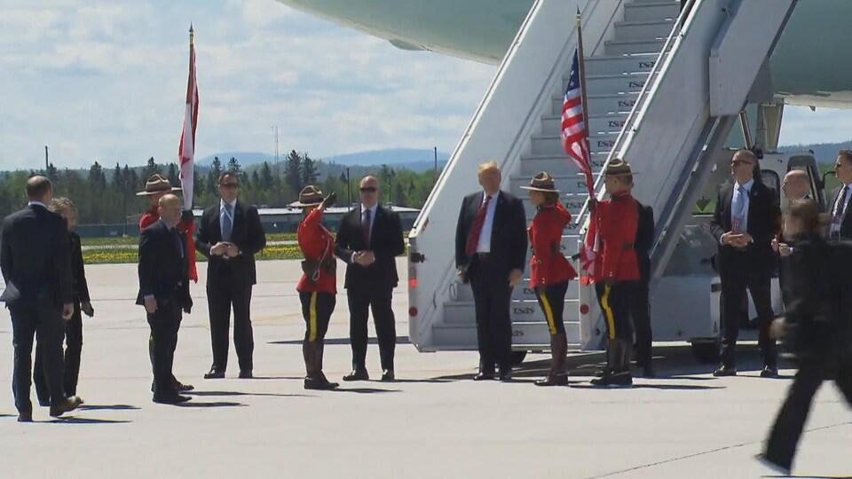 Donald Trump est entouré de policiers de la Gendarmerie royale du Canada qui le saluent.