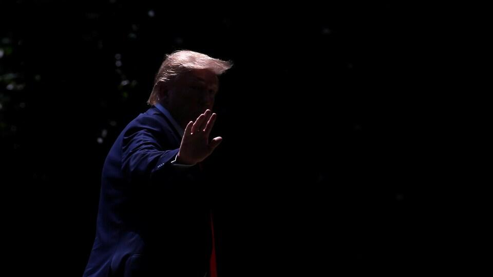 On ne distingue que la chevelure et la main de M. Trump sur cette photo prise dans la pénombre.