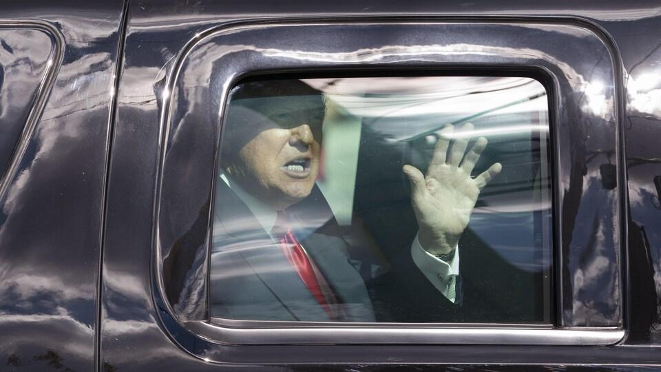 Donald Trump salue la foule de la main, derrière la vitre d'une voiture, à son arrivée à Mar-a-Lago, en Floride.