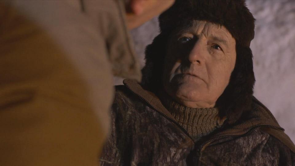 Un homme portant une tuque, regardant un autre homme de dos.