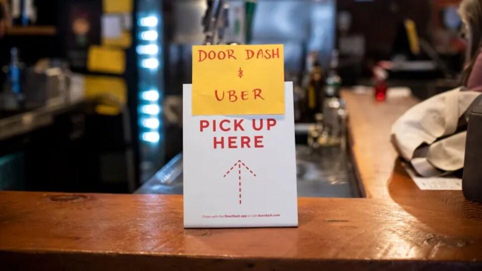 Une affiche placée sur un comptoir  indique aux livreurs et au consommateurs ou ramasser leur plat préparé commander sur une application.