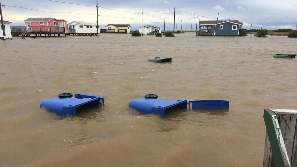 Des bacs de recyclage flottent sur l'eau dans une rue résidentielle inondée.