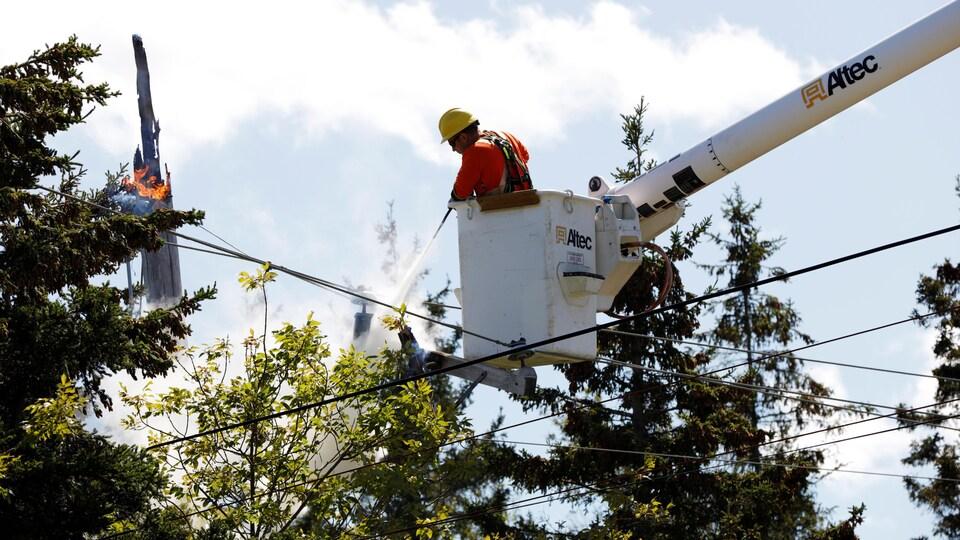 Un travailleur dans une nacelle utilise un extincteur pour éteindre un feu dans un transformateur électrique.