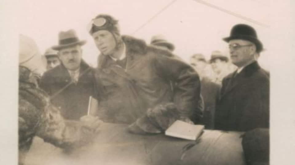 Un pilote, Charles Lindbergh, sort d'un avion entouré de gens (photo d'archives)