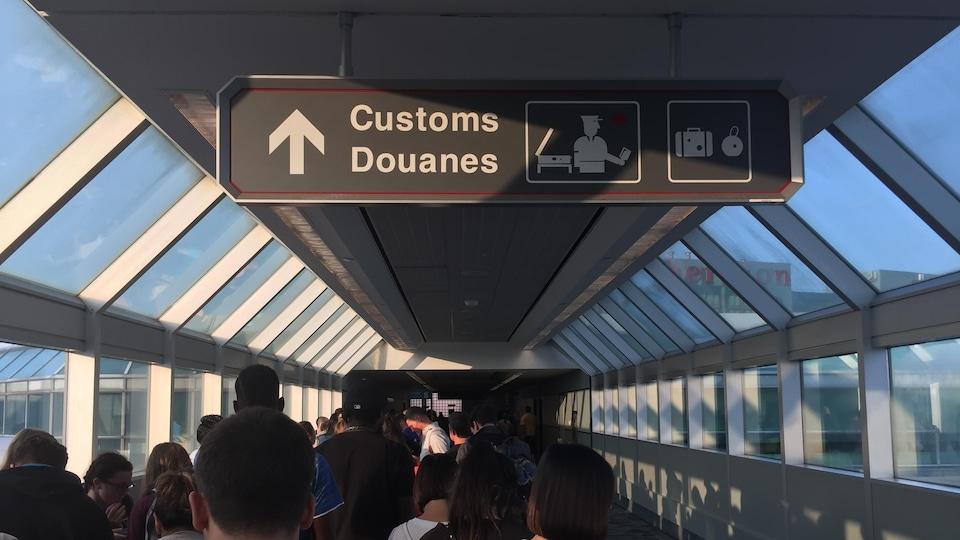 Plusieurs personnes attendent dans le corridor vitré menant aux douanes de l'aéroport international Pearson de Toronto; on voit une pancarte bilingue annonçant les douanes.