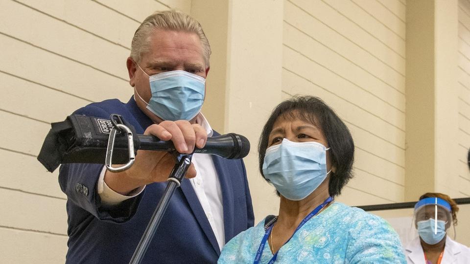 Le premier ministre de l'Ontario, Doug Ford, ajuste le microphone de la travailleuse de première ligne Anita Quidangen après qu'elle eut reçu la première dose du vaccin Pfizer-BioNTech à Toronto.