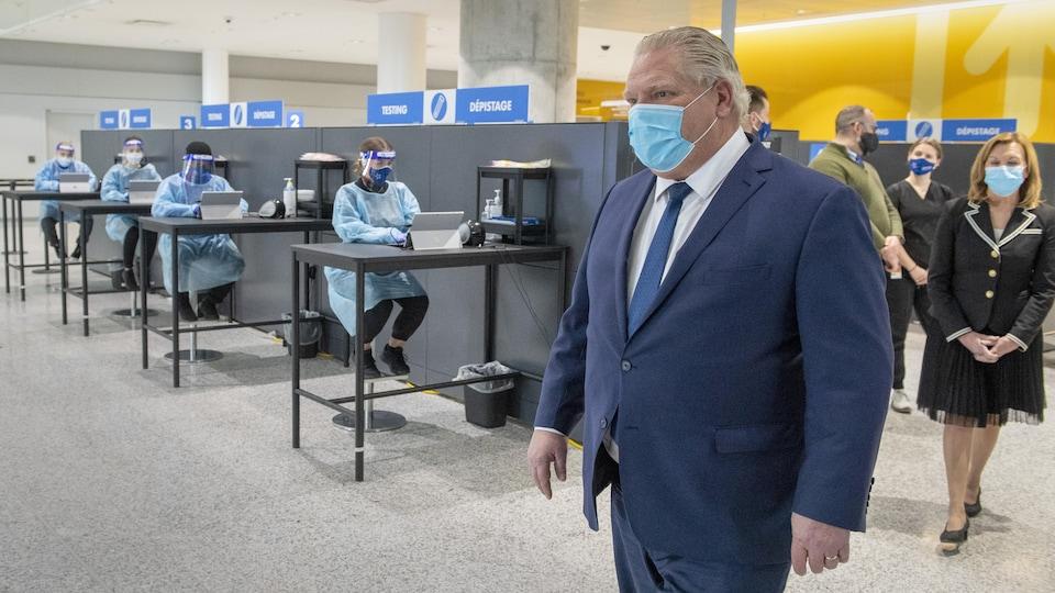 Doug Ford et la ministre de la Santé Christine Elliott devant des techniciennes qui font passer des tests à l'aéroport.