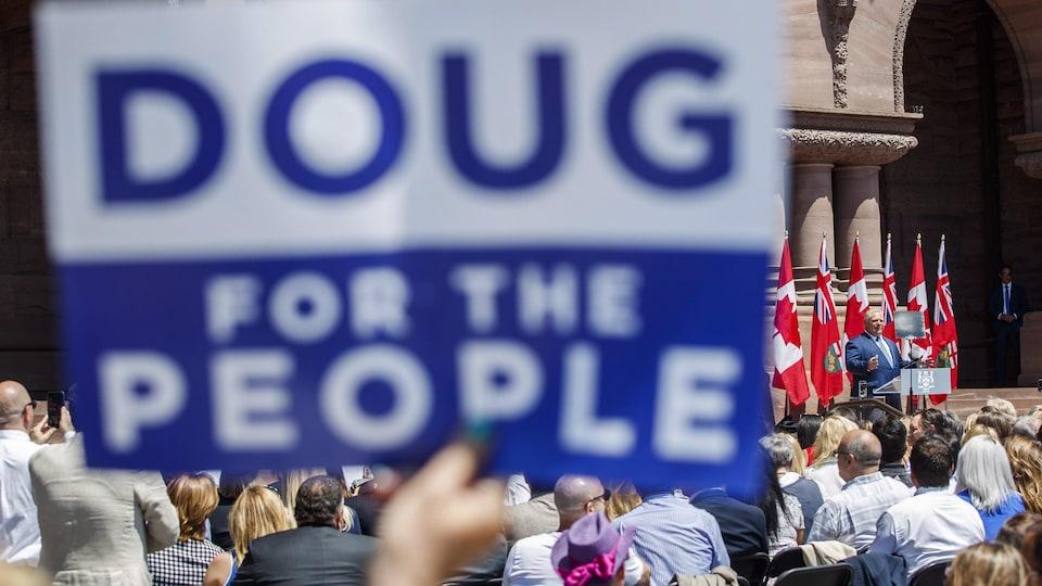 Des gens rassemblés à Toronto pour l'assermentation de Doug Ford, qui s'adresse à la foule.
