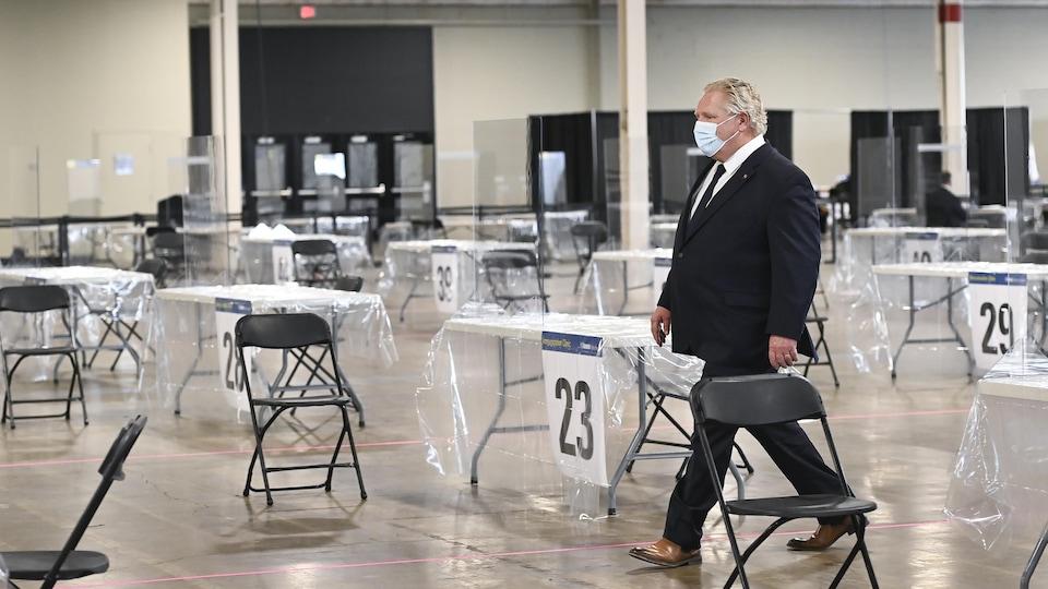 Doug Ford marchant seul au milieu d'une salle de vaccination de masse.